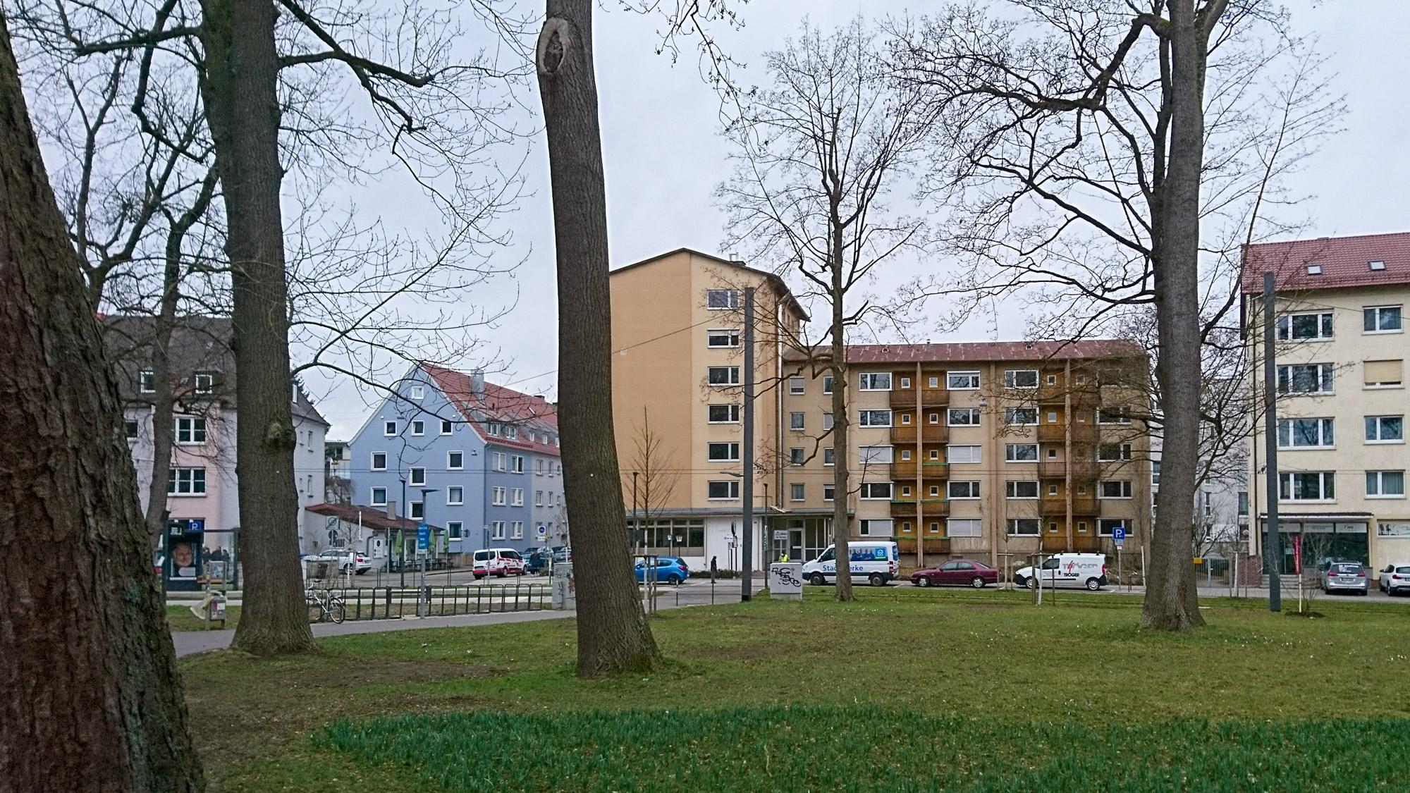 Grünfläche im Vordergrund, im Hintergrund ein braun-beige gestrichenes Wohngebäude aus den 50ern.