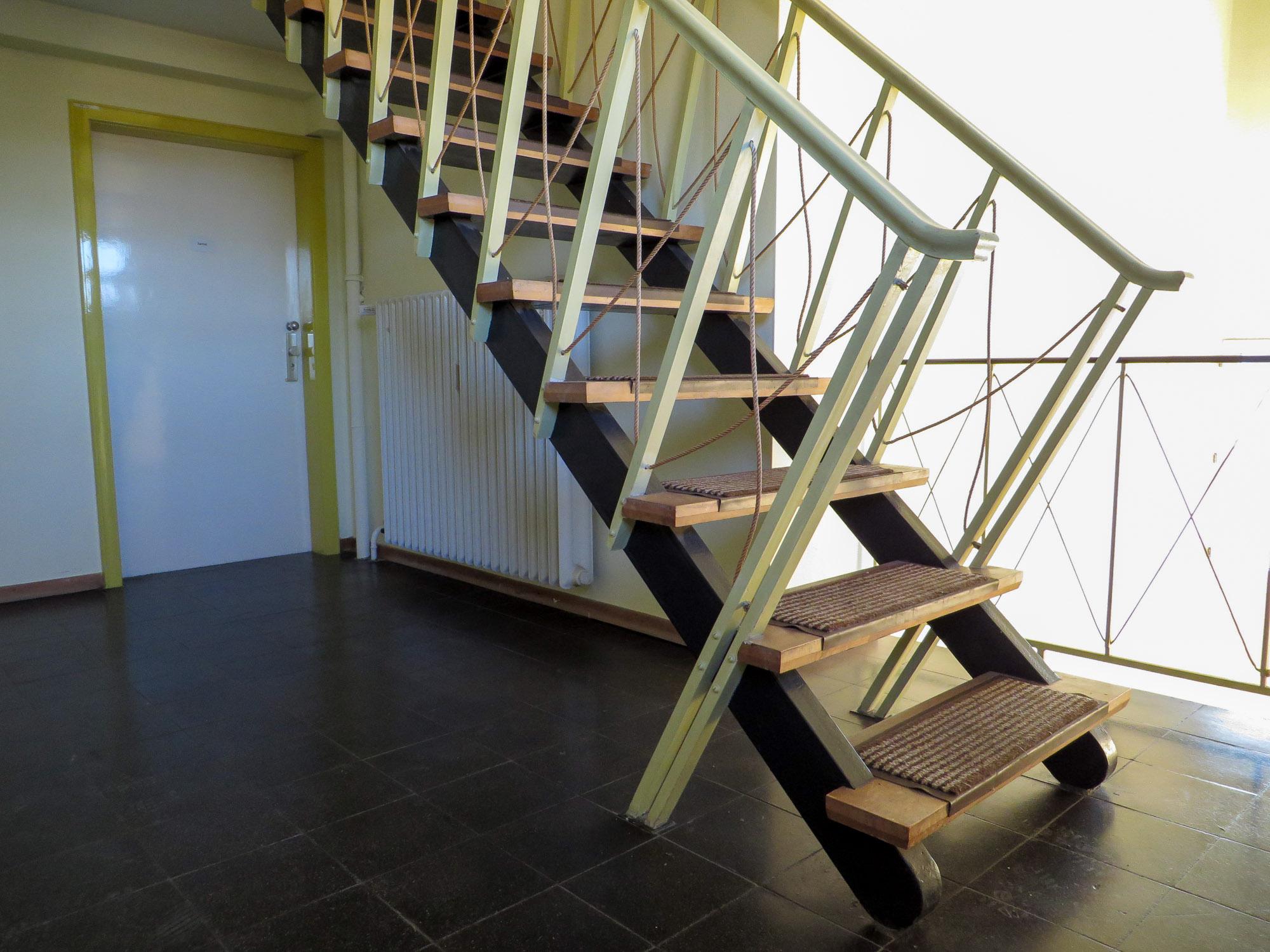 Steile Treppe vom Flur zum Dachboden. Die Form der Geländer erinnert an die Ausstattung eines Schiffs.