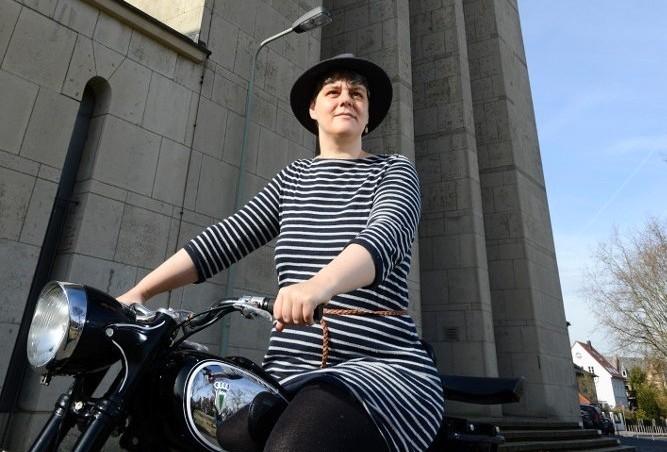 Frau in Ringelkleid mit Hut sitzt auf altem Motorrad vor einem Kirchengebäude